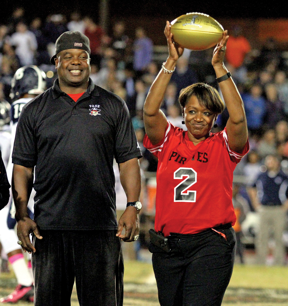 Former Page High & New York Giant running back Lee Rouson presents Page High School Principal, Patrice Faison, with a golden football during half time of the Page - Grimsley rivalry game. Photo by Joe Daniels / Carolina Peacemaker