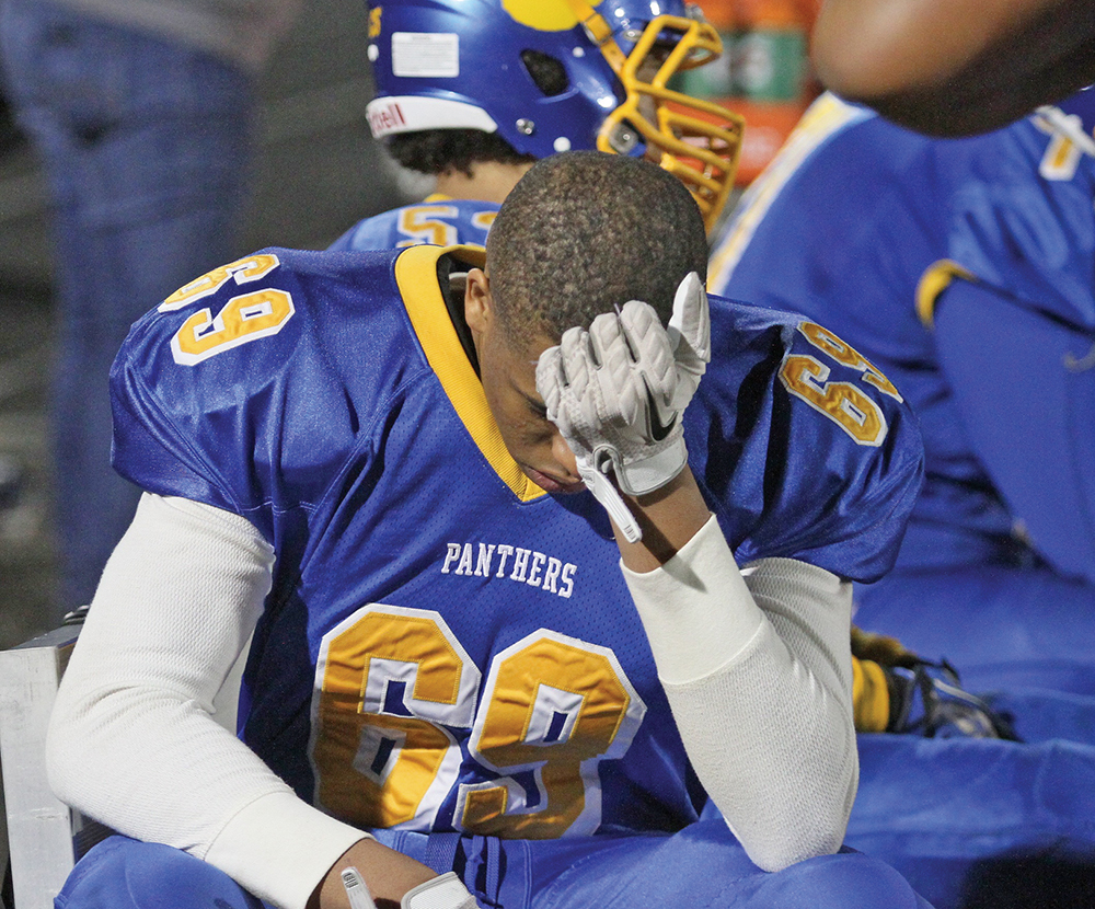 Dudley High School football player Brylyn Harris, a junior defensive lineman, sits and reflects on the Panthers 17-8 loss to Charlotte Catholic in the NCHSAA Class 4-A Regional. Photo by Joe Daniels