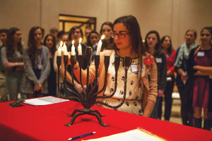Ellie Aronson, an American Hebrew Academy student, kindles Hanukkah lights in the Temple Emanuel chapel, as peers participate, and Muslim students observe. Photo courtesy of Ivan Cutler